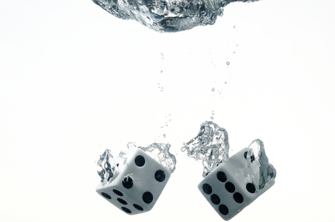 Dice dropped into the water, on a white background.